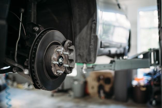 Carro com roda removida no elevador, disco de freio.