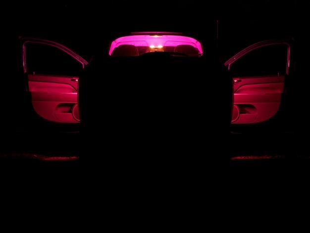Carro com uma luz vermelha dentro em uma noite escura
