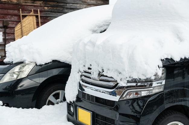 Carro congelado estacionado em casa, carros cobertos de neve no inverno.