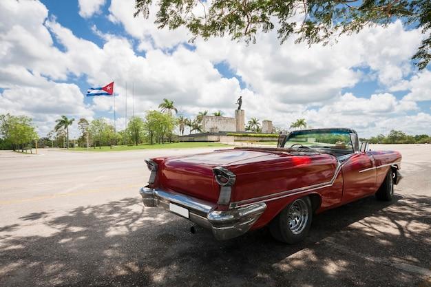 Carro conversível clássico com monumento e bandeira cubana no fundo