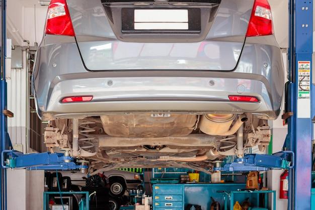 Carro da cidade no equipamento de levantamento na garagem que está sendo reparo e reparo, conceito da fixação do carro.