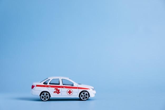 Carro de ambulância na parede azul. um serviço médico de emergência. modelo de veículo médico de brinquedo.