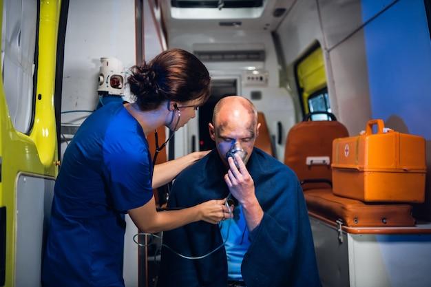 Carro de ambulância, uma jovem enfermeira está verificando o batimento cardíaco de um homem ferido em um cobertor