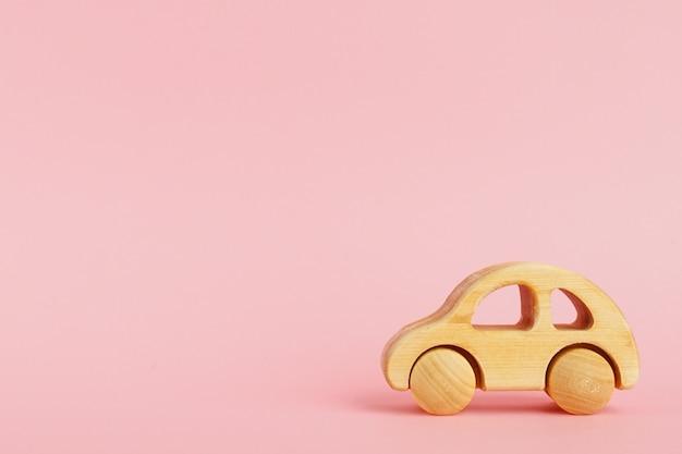 Carro de bebê de madeira em um fundo pastel rosa com copyspace.