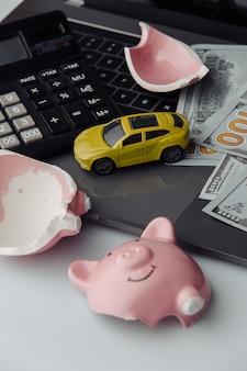 Carro de brinquedo amarelo e notas de dólares com cofrinho rosa quebrado no laptop