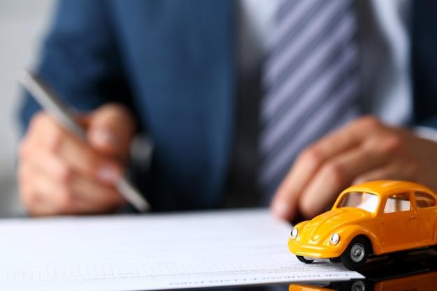 Carro de brinquedo amarelo irreconhecível na venda de documentos closeup