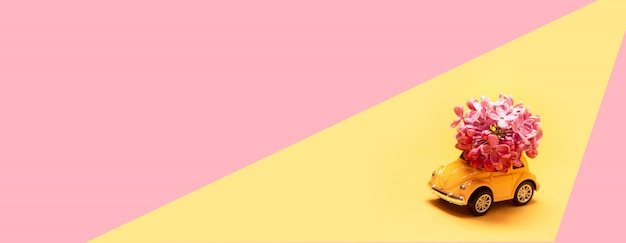 Carro de brinquedo amarelo oferece um buquê de lilás em amarelo rosa
