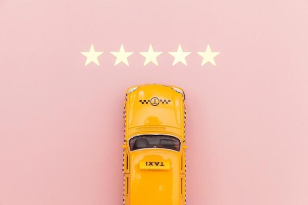 Carro de brinquedo amarelo táxi e classificação de 5 estrelas isolado no fundo rosa. aplicação por telefone do serviço de táxi para pesquisa on-line, chamando e reservando o conceito de táxi. símbolo de táxi copie o espaço.
