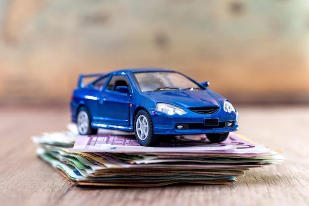 Carro de brinquedo azul com notas de euro na mesa