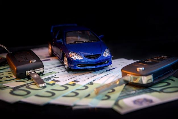 Carro de brinquedo azul nas notas de euro com chaves