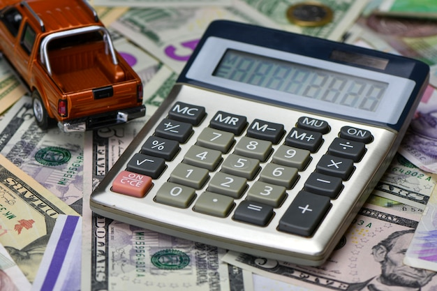 Carro de brinquedo calculadora e pick-up em uma variedade de notas de moeda nacional. do custo de compra, aluguel e manutenção de um carro.