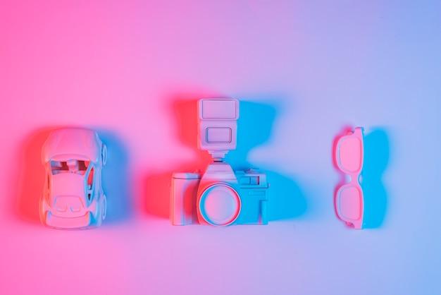Carro de brinquedo; câmera retro e espetáculo organizado em uma linha no pano de fundo rosa com efeito de luz azul