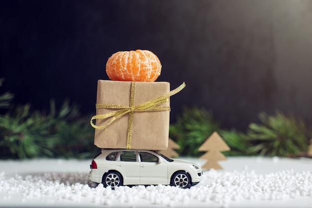 Carro de brinquedo carrega um presente para o natal e ano novo