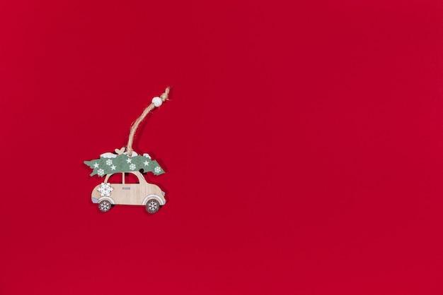 Carro de brinquedo carregando uma árvore de natal pendurada artesanal em um fundo vermelho