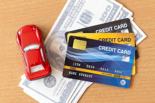 Carro de brinquedo, cartões de crédito e dólares na mesa de madeira. reembolso de dinheiro e conceito financeiro
