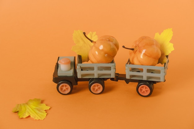 Carro de brinquedo com abóboras e folhas de outono em fundo laranja conceito de colheita de halloween e outono