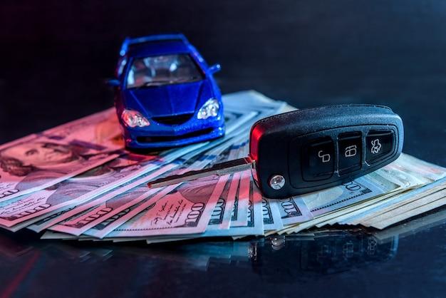 Carro de brinquedo com chave em dólares em fundo preto