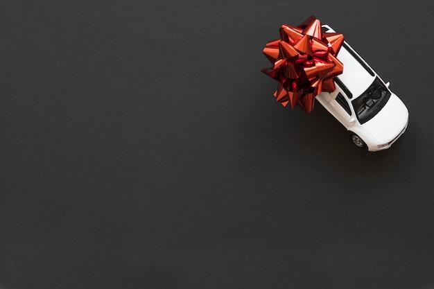 Carro de brinquedo com laço vermelho