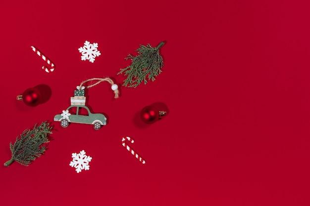 Carro de brinquedo de banner de natal com um presente para a árvore de natal, pirulito, floco de neve, bola em fundo vermelho
