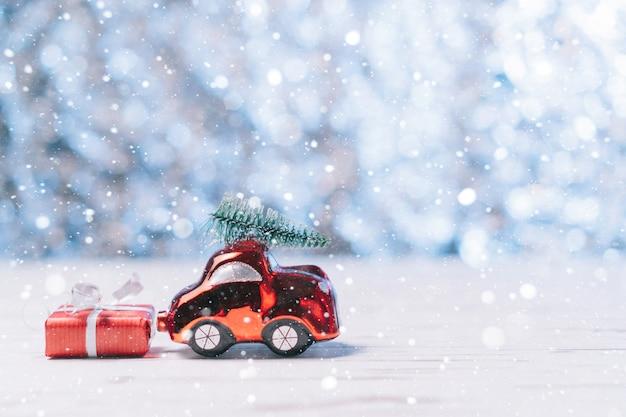 Carro de brinquedo de close-up carrega uma árvore de natal e uma caixa com um presente, conceito de natal e ano novo