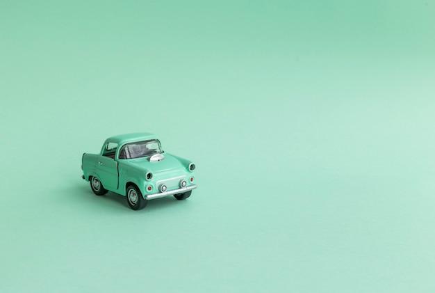 Carro de brinquedo de hortelã na estrada em um fundo neo hortelã.