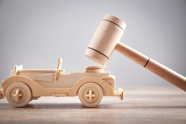 Carro de brinquedo de madeira e martelo de juiz.