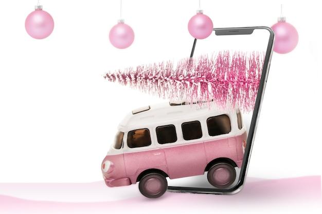 Carro de brinquedo de microônibus infantil carrega uma árvore de natal da floresta. de um telefone celular. entrega de presentes de natal e árvores de natal, cor rosa.