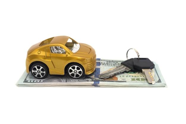 Carro de brinquedo, dólares e chaves isolados no fundo branco. conceito de compra de automóveis.