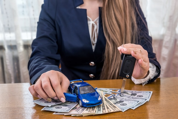 Carro de brinquedo e chaves em mãos femininas em notas de dólar