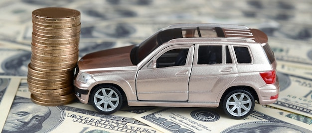 Carro de brinquedo em acidente em notas de 100 dólares e pilha de moedas de ouro