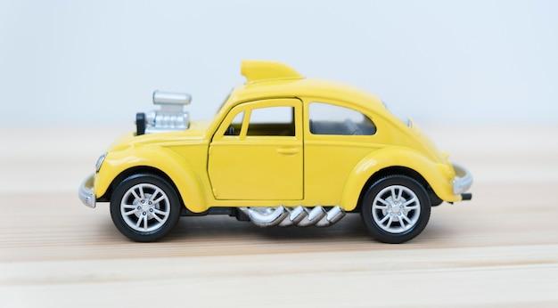 Carro de brinquedo em fundo branco em fundo de madeira.