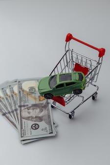 Carro de brinquedo em uma cesta de compras e dinheiro. imagem vertical.