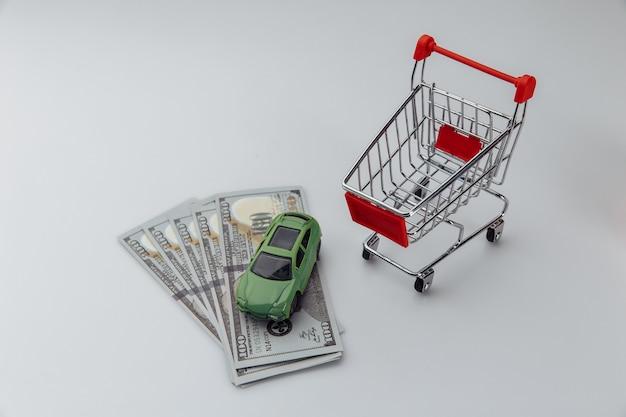 Carro de brinquedo em uma cesta de compras e notas de dólar em um fundo branco.