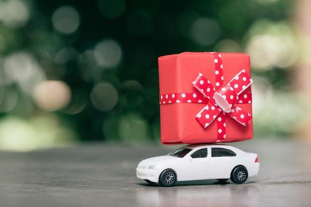 Carro de brinquedo, entregando a caixa de presente.