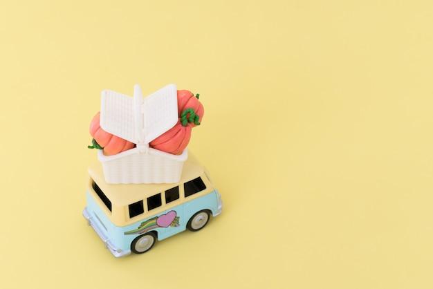 Carro de brinquedo entregando abóboras contra amarelo