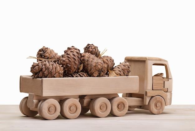 Carro de brinquedo feito de madeira com pinhas