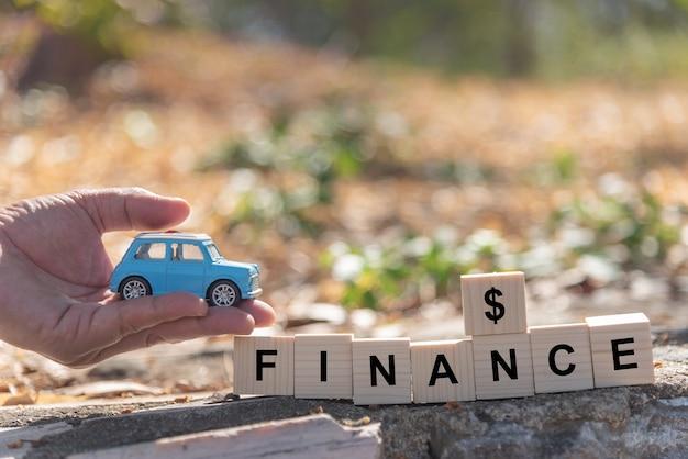 Carro de brinquedo na mão, homem com blocos de madeira, finanças, palavra, conceito financeiro