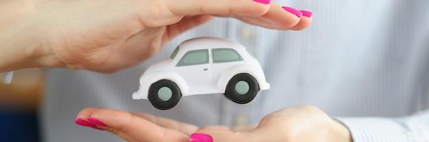 Carro de brinquedo nas mãos femininas de corretor de seguros