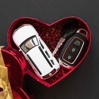Carro de brinquedo perto de chaves de alarme na caixa de presente