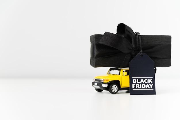 Carro de brinquedo preto sexta-feira carregando presente