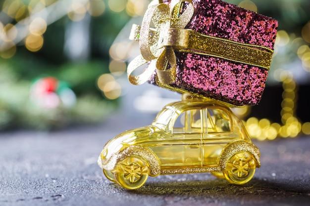 Carro de brinquedo retrô amarelo entregando presentes de natal ou ano novo em fundo escuro