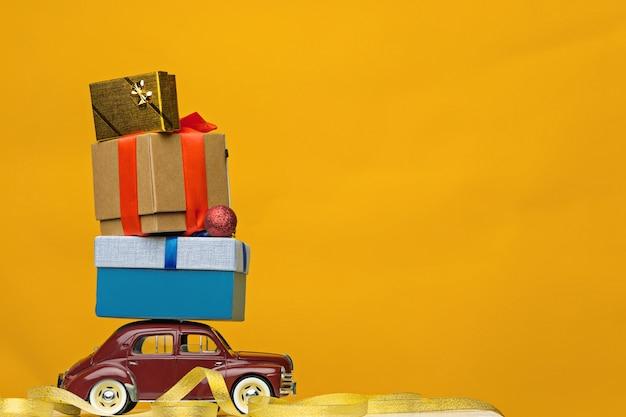 Carro de brinquedo retrô azul entregando presentes de natal ou ano novo, em amarelo