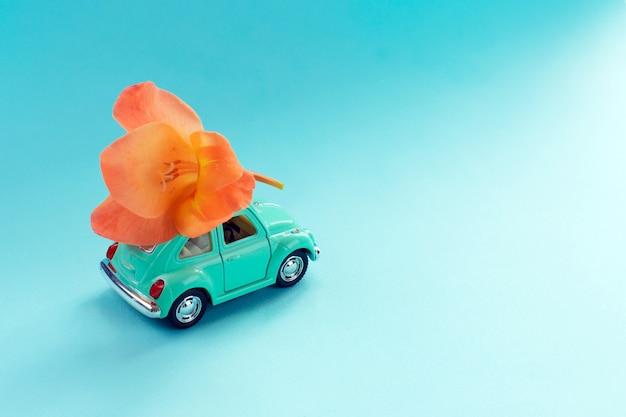 Carro de brinquedo retrô com flor no telhado
