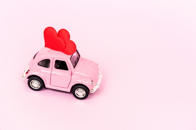 Carro de brinquedo retrô rosa entregando coração de artesanato para dia dos namorados