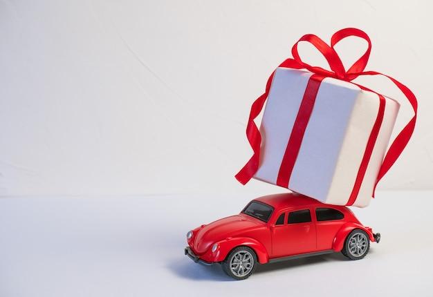 Carro de brinquedo retrô vermelho entregando presentes de natal ou ano novo no telhado em um fundo branco