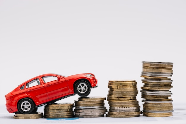 Carro de brinquedo subindo na pilha crescente de moedas contra o fundo branco