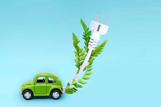 Carro de brinquedo verde como carro elétrico ev com cabo branco e folhas verdes em azul