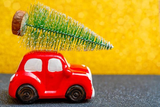 Carro de brinquedo vermelho carrega uma árvore de natal para o feriado.