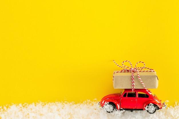 Carro de brinquedo vermelho carregando uma caixa de presente de natal