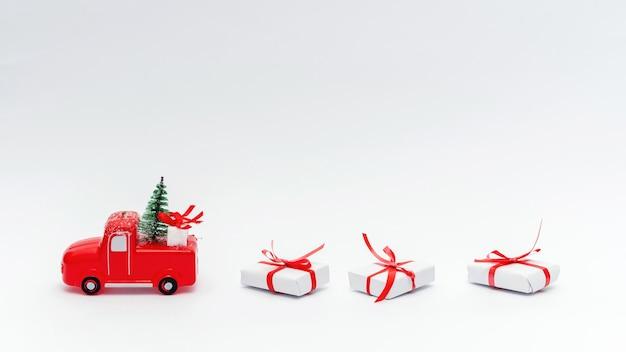 Carro de brinquedo vermelho com árvore de natal e presentes. fundo azul